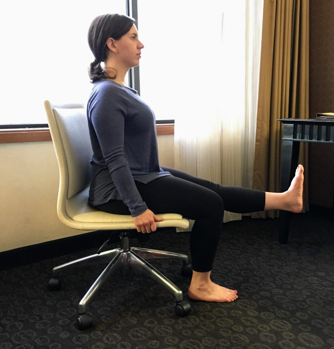 Woman sitting in chair with one foot flat on floor and one foot straight out