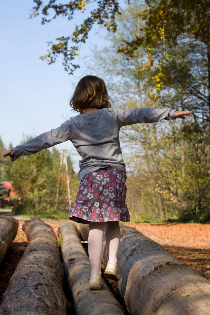 girl balancing on log