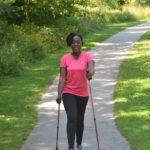 African American woman walking using Urban Poling Activator poles, which can help with vestibular compensation.